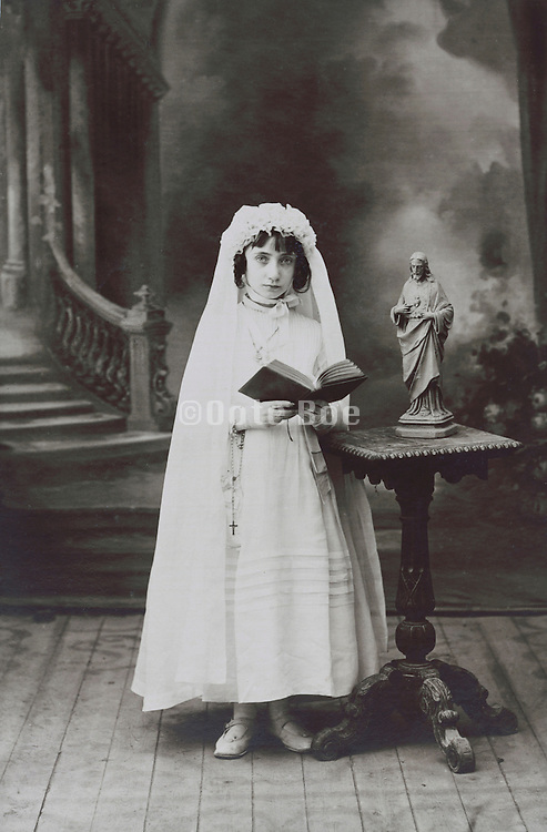 girl posing reading the bible to commemorate her holy communion