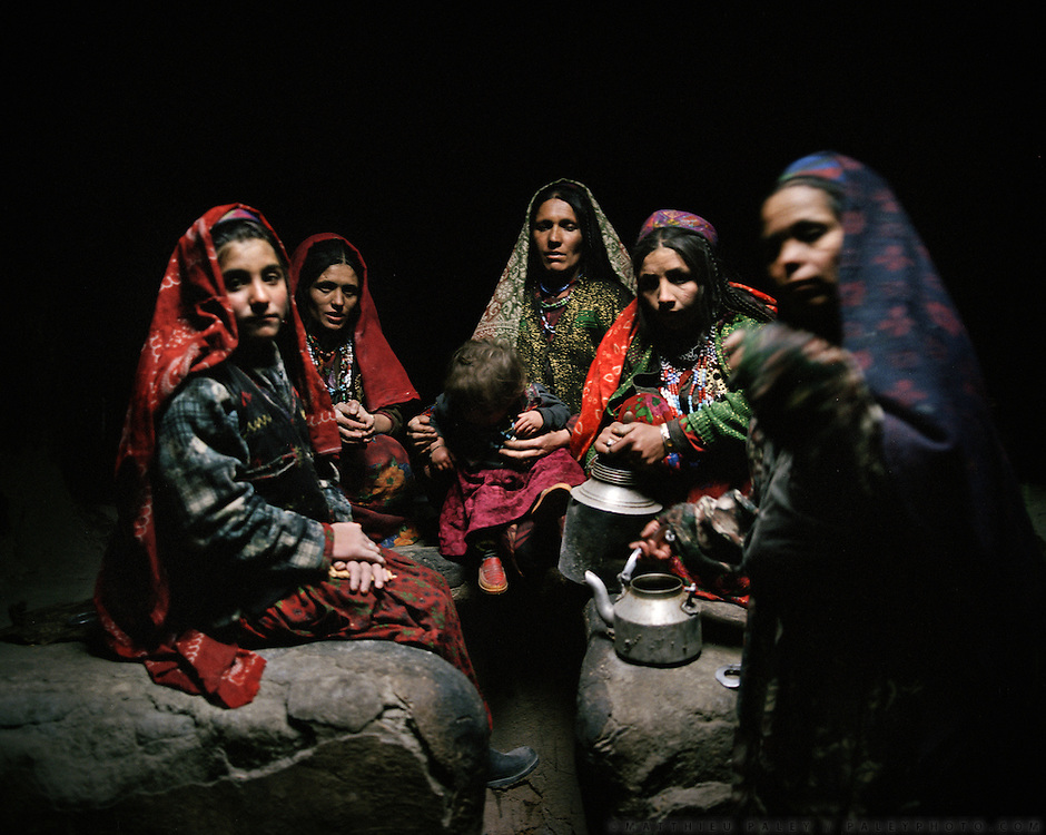 Wakhi men and women inside a typical Wakhi house, belonging to Qatch Baig. Light comes from an opening in the roof. Sarhad village..Winter expedition through the Wakhan Corridor and into the Afghan Pamir mountains, to document the life of the Afghan Kyrgyz tribe. January/February 2008. Afghanistan