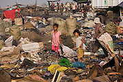RUBBISH DUMP RECYCLING. South East Asia, Cambodia, Phnom Penh. Smokey Mountain, Steung Mean Chey, is Phnom Penh's municipal rubbish dump. Thousands work there, some 600 minors and 2000 adults, recycling the city's rubbish, dumped there by garbage trucks every day. The dump is notorious as many very young children work there. People eat and sleep overnight in the rubbish and fumes, under plastic tarpaulins or in the open air. They work 24 hours a day, like miners, with headlamps at night, collecting plastic, metals, wood, cloth & paper, which they sort and clean, weigh and sell, to be carried away for recycling. A day's work typically brings less than a dollar per person. One and a half to two dollars per day per family. The overpowering, acrid odour of grey smokey fumes blows across the dump, from which the place gets its name 'Smokey Mountain'. It can be smelt miles away. The shantytowns and squats, the recycling worker's homes butt onto or are inside the dump itself. There is no running water, sanitation and many are ill. Children often work with friends or relatives. Religious and ngo's help some children, but this is often resisted by families who need the extra income they generate.///Young girls, friends Li and Jakoy, dragging sacks of materials, make their way through Smokey Mountain, on their quest for materials to recycle