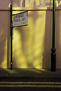 Yellow light reflected from an adjacent building on to a wall in London's Soho.
