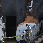 """2/17/11 -- BRUNSWICK, Maine.  Margaret Burke of Brunswick walks down the stairs of her apartment on Thursday morning after fire consumed her building on Union St. on Wednesday night. Her husband, Danny Burke, was burned over 35% of his body, according to neighbors.  """"It was scary,"""" she said. """" I don't know what's going to happen."""" The family lost one cat, but firefighters saved one and revived another. """"I thought we'd lost him too - but they came back a little while later and he was better.""""  Photo by Roger S. Duncan."""