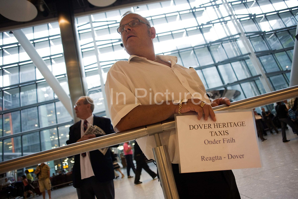 """From a low angle, we see a greeting driver from Dover Heritage Taxis who awaits his passenger to arrive off a flight from Turkey. In the hectic international arrivals concourse of Heathrow Airport's Terminal 5, the man holds up a name board to attract the attention of the man who is a member of a cruise ship's crew that is due to sail from the sea port of Dover. From writer Alain de Botton's book project """"A Week at the Airport: A Heathrow Diary"""" (2009)."""