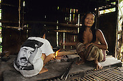 1991: Semi-nomadic Penan in traditional 'sulap' temporary settlement. A woman tends to the fires whilst her son watches, wearing a Saddam Hussein T-shirt. Many Christian and Muslims tried to convert the Dayak tribes, who are mainly Christian and Animist. The Muslims don't have much luck because the natives like to eat wild boar pig-meat. Belaga district, Sarawak, Borneo<br /> <br /> Tropical rainforest and one of the world's richest, oldest eco-systems, flora and fauna, under threat from development, logging and deforestation. Home to indigenous Dayak native tribal peoples, farming by slash and burn cultivation, fishing and hunting wild boar. Home to the Penan, traditional nomadic hunter-gatherers, of whom only one thousand survive, eating roots, and hunting wild animals with blowpipes. Animists, Christians, they still practice traditional medicine from herbs and plants. Native people have mounted protests and blockades against logging concessions, many have been arrested and imprisoned.