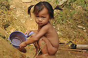 Portrait of a young girl in Laos playing in the mud