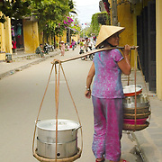Woman carrying pots and pans in the streets of Hoi An