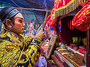 "14 MAY 2015 - BANGKOK, THAILAND:  A Chinese opera performer prays at a small alter set up backstage at the Pek Leng Keng Mangkorn Khiew Shrine in the Khlong Toey slum in Bangkok. Chinese opera was once very popular in Thailand, where it is called ""Ngiew."" It is usually performed in the Teochew language. Millions of Chinese emigrated to Thailand (then Siam) in the 18th and 19th centuries and brought their culture with them. Recently the popularity of ngiew has faded as people turn to performances of opera on DVD or movies. There are still as many 30 Chinese opera troupes left in Bangkok and its environs. They are especially busy during Chinese New Year and Chinese holiday when they travel from Chinese temple to Chinese temple performing on stages they put up in streets near the temple, sometimes sleeping on hammocks they sling under their stage. Most of the Chinese operas from Bangkok travel to Malaysia for Ghost Month, leaving just a few to perform in Bangkok.      PHOTO BY JACK KURTZ"