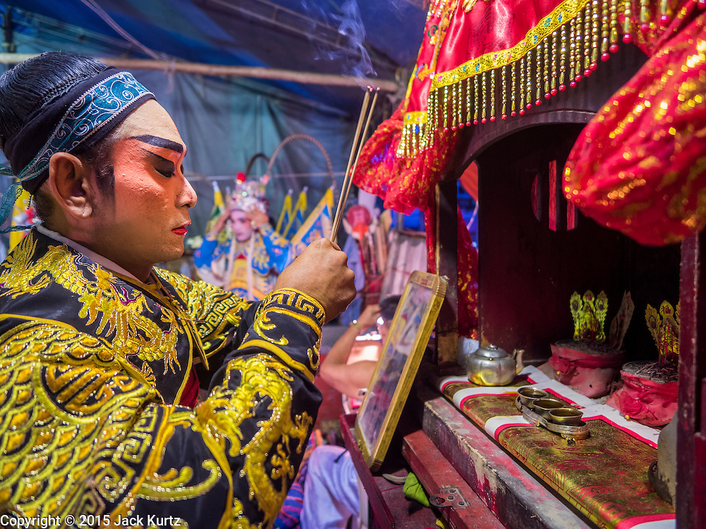"""14 MAY 2015 - BANGKOK, THAILAND:  A Chinese opera performer prays at a small alter set up backstage at the Pek Leng Keng Mangkorn Khiew Shrine in the Khlong Toey slum in Bangkok. Chinese opera was once very popular in Thailand, where it is called """"Ngiew."""" It is usually performed in the Teochew language. Millions of Chinese emigrated to Thailand (then Siam) in the 18th and 19th centuries and brought their culture with them. Recently the popularity of ngiew has faded as people turn to performances of opera on DVD or movies. There are still as many 30 Chinese opera troupes left in Bangkok and its environs. They are especially busy during Chinese New Year and Chinese holiday when they travel from Chinese temple to Chinese temple performing on stages they put up in streets near the temple, sometimes sleeping on hammocks they sling under their stage. Most of the Chinese operas from Bangkok travel to Malaysia for Ghost Month, leaving just a few to perform in Bangkok.      PHOTO BY JACK KURTZ"""