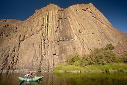 North America, United States, Oregon, John Day River, boy (age 11) rowing pontoon raft under huge columnar basalt rock formation.  MR