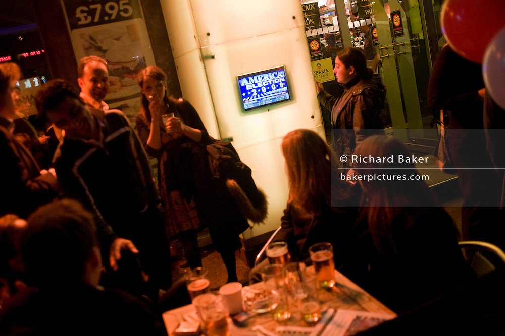 Guests of CNN watch outdoor TV during the 2008 political election which saw Barack Obama become the first black president