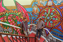 Two male residents standing on stairs in Young Persons' Resettlement hostel talking,