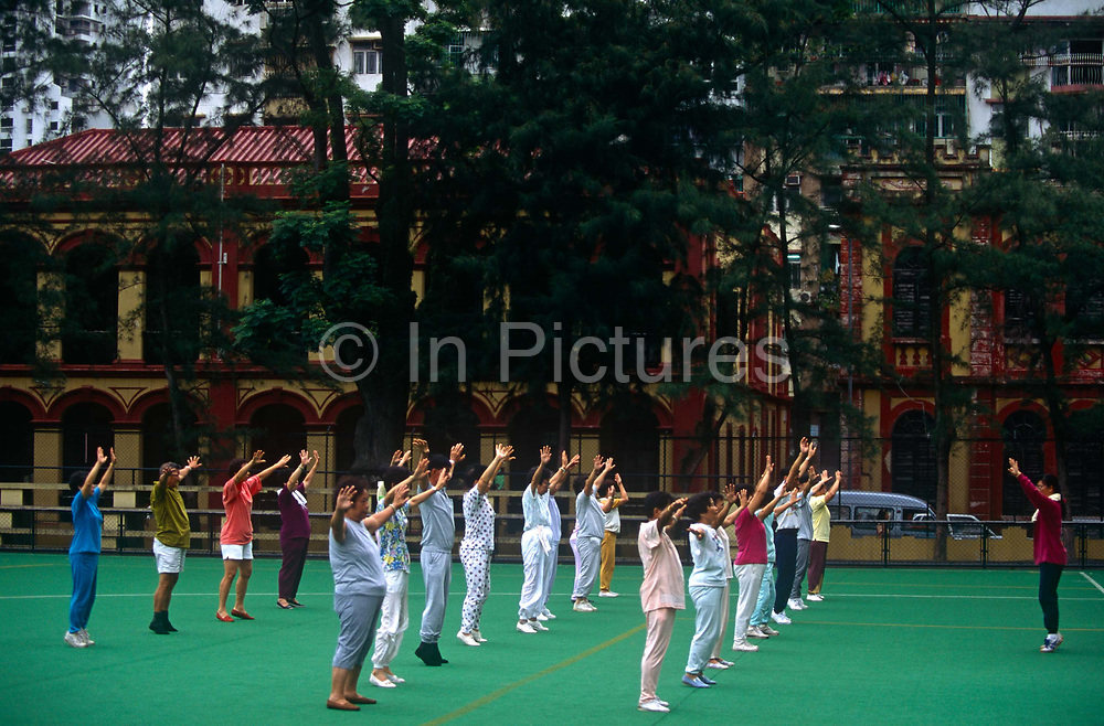 With colonial Portuguese architecture in the background, older women and a few men participate in a group exercise on an astroturf-covered sports ground, on 10th August 1994, in Macau, China. The Macau Special Administrative Region is one of the two special administrative regions of the Peoples Republic of China PRC, along with Hong Kong. Administered by Portugal until 1999, it was the oldest European colony in China, dating back to the 16th century. The administrative power over Macau was transferred to the Peoples Republic of China PRC in 1999, 2 years after Hong Kongs own handover.