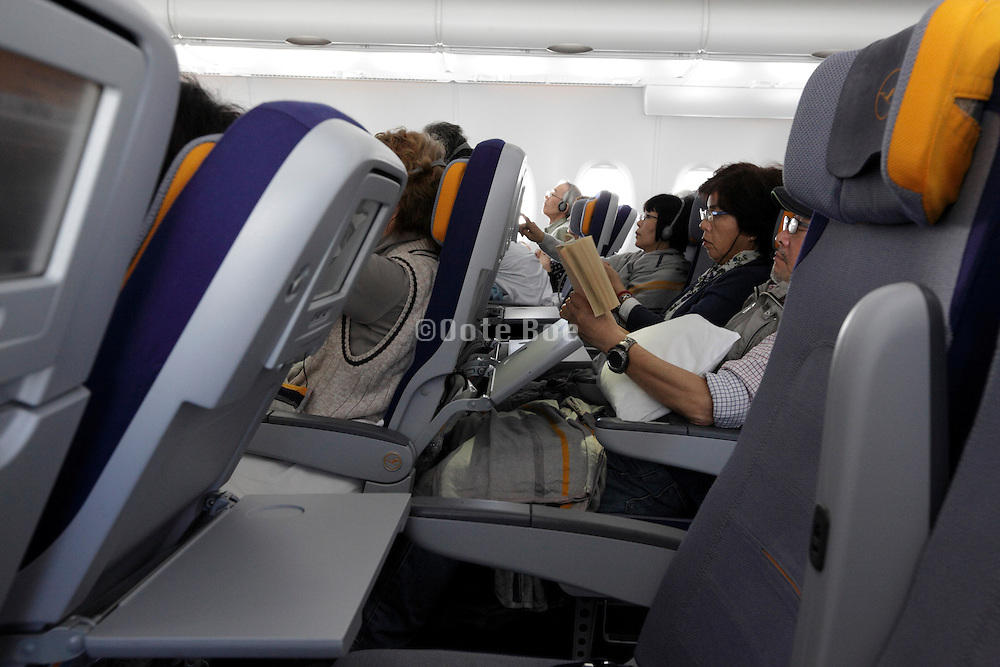 passenger relaxing during flight in a not fully occupied economy class A380 Airbus