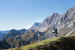 Mountain biker admiring scenic view on top of mountain, Tyrol, Austria