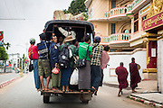 14 JUNE 2013 -  PATHEIN, AYEYARWADY, MYANMAR: Buddhist monks walk away from a crowded truck used as a bus they just got off of in Pathein, Myanmar. Pathein, sometimes also called Bassein, is a port city and the capital of the Ayeyarwady Region, Burma. It lies on the Pathein River (Bassein), which is a western branch of the Irrawaddy River. It's the fourth largest city in Myanmar (Burma) about 190 km west of Yangon.   PHOTO BY JACK KURTZ