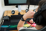 A young gamer with headphones boy playing a computer game on a powerful desktop computer Model Release Available