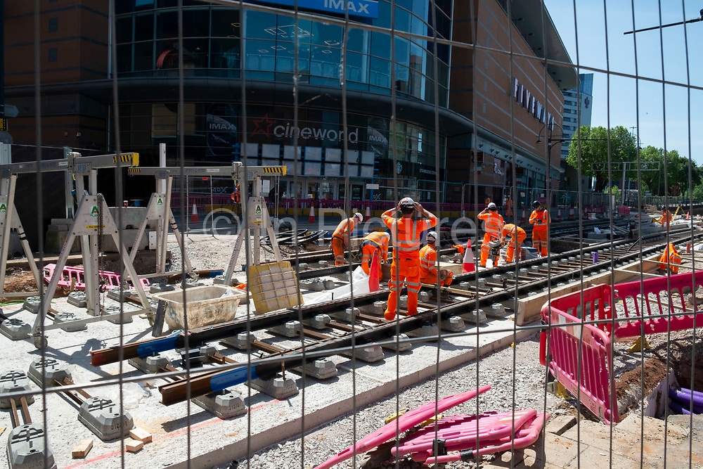 Workers laying new tram tracks on Broad Street as the Coronavirus lockdown continues, the city centre is still very quiet while more traffic and people are returning, and with restrictions due to be relaxed further in the coming days, the quiet city may be coming to an end as businesses are set to start to reopen soon on 27th May 2020 in Birmingham, England, United Kingdom. The Midland Metro is a light-rail tram line in the county of West Midlands, England, operating between the cities of Birmingham and Wolverhampton via the towns of West Bromwich and Wednesbury. The line operates on streets in urban areas, and reopened conventional rail tracks that link the towns and cities. Coronavirus or Covid-19 is a respiratory illness that has not previously been seen in humans. While much or Europe has been placed into lockdown, the UK government has put in place more stringent rules as part of their long term strategy, and in particular social distancing.