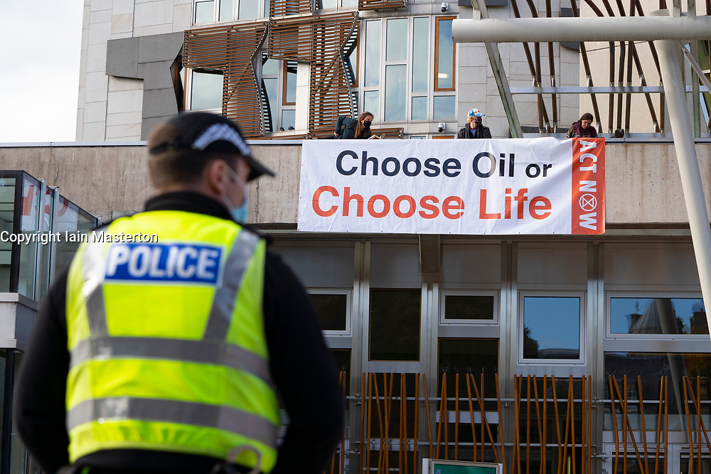 """Edinburgh, Scotland, UK. 8 October 2020. Extinction Rebellion stage protest on roof of Scottish Parliament building at Holyrood in Edinburgh.  The group, Extinction Rebellion Scotland have hung a banner reading """"Choose Oil or Choose Life""""  in a protest against fossil fuels. Iain Masterton/Alamy Live News"""