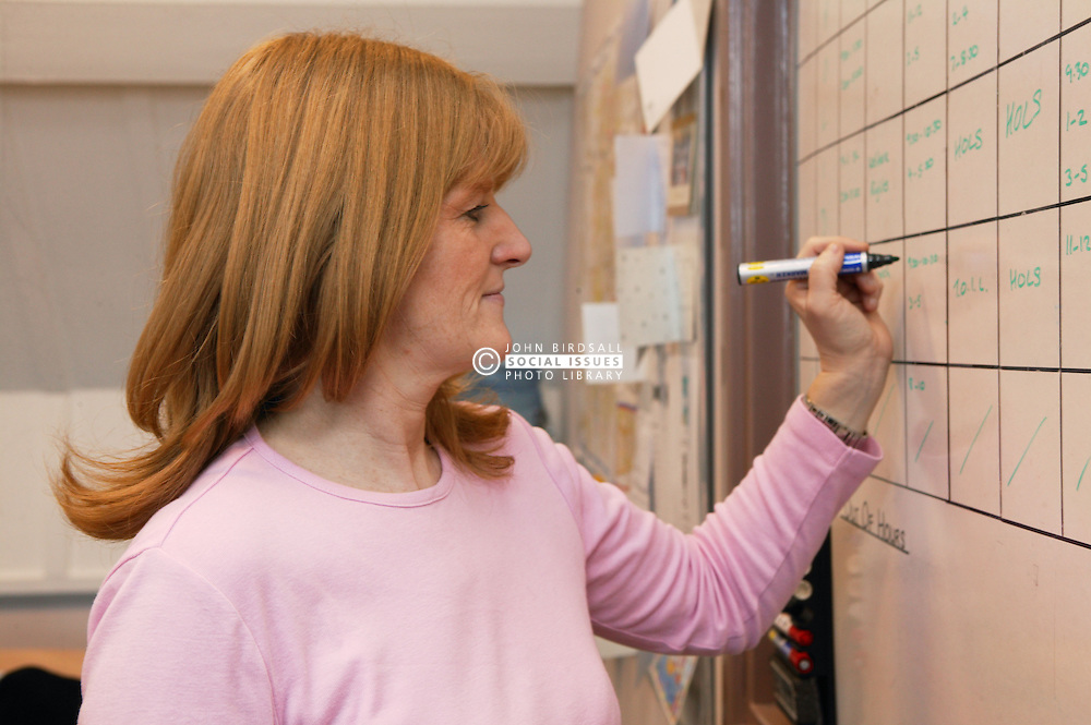 Single parent at work writing on notice board in her office,