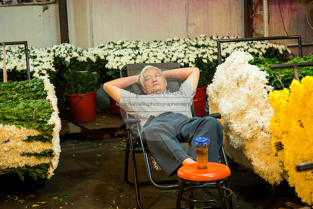 Flower seller asleep at the Wansheng Market in Shanghai, China
