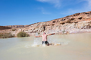 man swims in the lake at Timna natural and historic park, Israel, The Timna Valley is located in the southwestern Arava, some 30 km. north of the Gulf of Eilat.