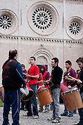 Drummers rehearse for the annual Calendimaggio spring festival to commemorate Holy Week in front of the rose windows of the Church of Saint Peter, Assisi, Umbria, Italy.