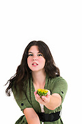 Young female teen offers the viewer a sunflower in the palm of her hand. Focus on flower