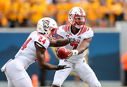 Sep 14, 2019; Morgantown, WV, USA; North Carolina State Wolfpack quarterback Matthew McKay (7) hands the ball off to North Carolina State Wolfpack running back Zonovan Knight (24) during the first quarter against the West Virginia Mountaineers at Mountaineer Field at Milan Puskar Stadium. Mandatory Credit: Ben Queen-USA TODAY Sports