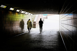 Two people walking through a dark pedestrian subway. Basildon Essex