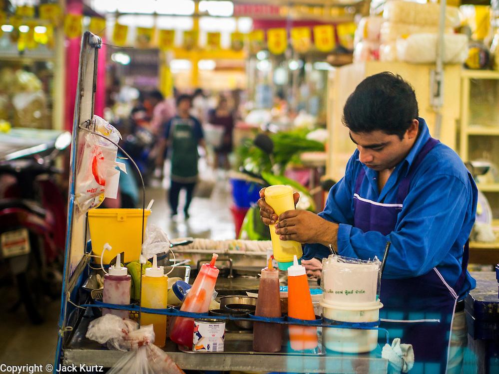 12 OCTOBER 2012 - NAKHON PATHOM, NAKHON PATHOM, THAILAND: A snack vendor waits for customers in the Nakhon Pathom market.   PHOTO BY JACK KURTZ