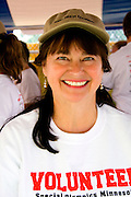 Happy woman volunteer smiling at award table. Special Olympics U of M Bierman Athletic Complex. Minneapolis Minnesota USA
