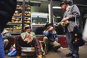 Romanies dressed like cowboys, share conversation with a gentleman passer-by, on Brick Lane Market. London, England 1996.