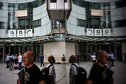 © Licensed to London News Pictures. 19/07/2017. London, UK. A reflection in a window of people arriving at  BBC Broadcasting House in London where the BBC annual report is due to be published later this morning. The BBC is set to reveal for the first time the salaries of stars earning more than £150,000. Photo credit: Ben Cawthra/LNP