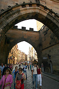 Czeck Republic - Prague, visitors and locals pass under the arch of the Mala Strana Bridge tower as they enter the Charles Bridge.