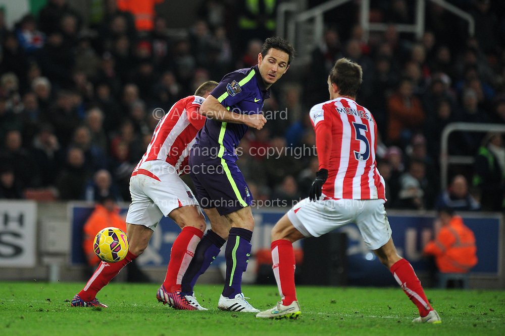 Frank Lampard of Manchester city © tries to get past Stoke city's Phil Bardsley (l) and Marc Muniesa (r). Barclays Premier League match, Stoke city v Manchester city at the Britannia Stadium in Stoke on Trent , Staffs on Wed 11th Feb 2015.<br /> pic by Andrew Orchard, Andrew Orchard sports photography.