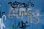 Guns graffiti on a blue wooden door on 31st March 2021 in Birmingham, United Kingdom. Gun crime in the UK increased by 4% year on year from 2018 to 2019.
