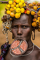 Mursi tribe woman with clay lip plate and headdress, Lower Omo Valley, Mago National Park,  Ethiopia.