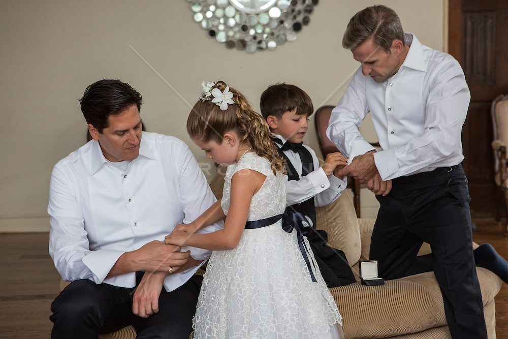 gay couple helping dressing with their two young children for gay wedding