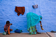 An Indian woman, sweeps her back yard as her child prepares to leave for school lessons, Salawas, Rajasthan, India.