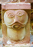 Norman Romanesque exterior corbel no 49  - sculpture of  an alien like chinless bald headed figure. Its perfectly round mouth is filled with a ball like object and may be a moral warning about talking too much. The Norman Romanesque Church of St Mary and St David, Kilpeck Herefordshire, England. Built around 1140 .<br /> <br /> Visit our MEDIEVAL PHOTO COLLECTIONS for more   photos  to download or buy as prints https://funkystock.photoshelter.com/gallery-collection/Medieval-Middle-Ages-Historic-Places-Arcaeological-Sites-Pictures-Images-of/C0000B5ZA54_WD0s