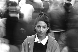 Young girl standing among blurred crowd of people,