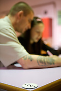 A prisoner spends time with his family during visiting time. HMP Wandsworth, London, United Kingdom