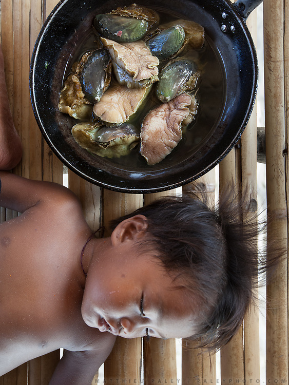 A young boy sleeps near a pot of abalone  that is being prepared for lunch.