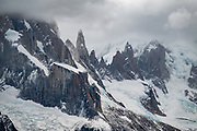 """Clouds swirl around the peaks of Aguja Bífida and Cuatro Dedos in the Cerro Torre Group, seen from Mirador """"Loma del Pliegue Tumbado"""" (""""hill of the collapsed fold""""). To reach the viewpoint, we hiked 19 km (11.9 mi) with 1170 meters (3860 ft) cumulative gain from El Chalten, in Los Glaciares National Park, Santa Cruz Province, Argentina, Patagonia, South America. Chaltén comes from a Tehuelche word meaning """"smoking mountain"""", due to frequent clouds. Los Glaciares National Park and Reserve are honored on UNESCO's World Heritage List."""