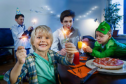 Playful young boys celebrating birthday with sparklers