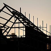 silhoueted timber house construction with sunset background