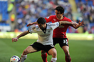 Fulham's Giorgos Karagounis (l) holds off Cardiff's Fabio Da Silva. Barclays Premier league, Cardiff city v Fulham at the Cardiff city Stadium in Cardiff , South Wales on Sat 8th March 2014. pic by Andrew Orchard, Andrew Orchard sports photography