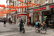 Deliveroo cycle couriers in Chinatown on 25th May 2021 in London, United Kingdom. As the coronavirus lockdown continues its process of easing restrictions, more and more people are coming to the West End as more businesses open.