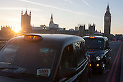 With a setting sun, Big Ben and the Houses of Parliament in the distance, two black London taxies are stopped on Westminster Bridge awaiting a fare, on 30th November 2016, in London, England.