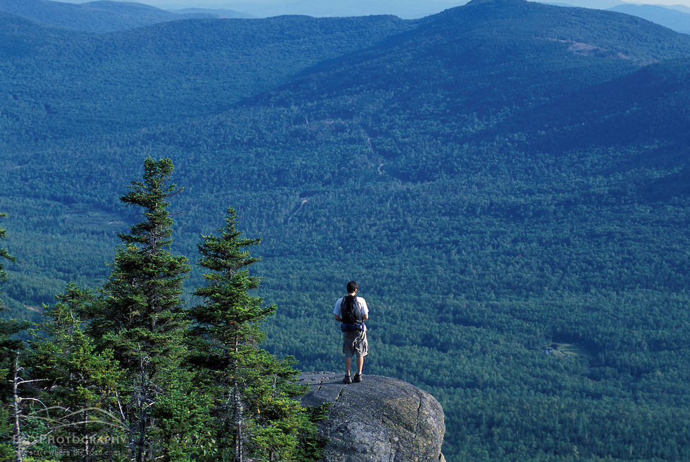 Weld, ME. A hiker stands on a ledge near the west peak of Tumbledown Mountain. Northern Forest.