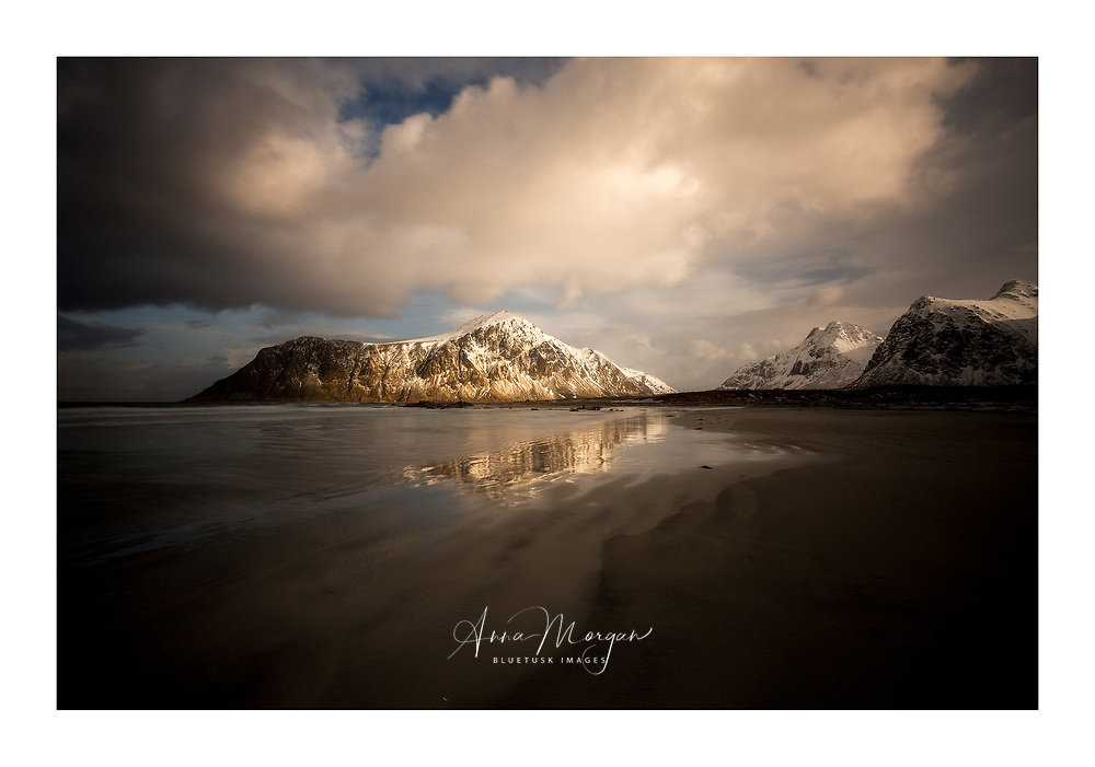 Reflections on the wet sand, Flakstad beach in winter in beautiful afternoon light, Lofoten, Norway